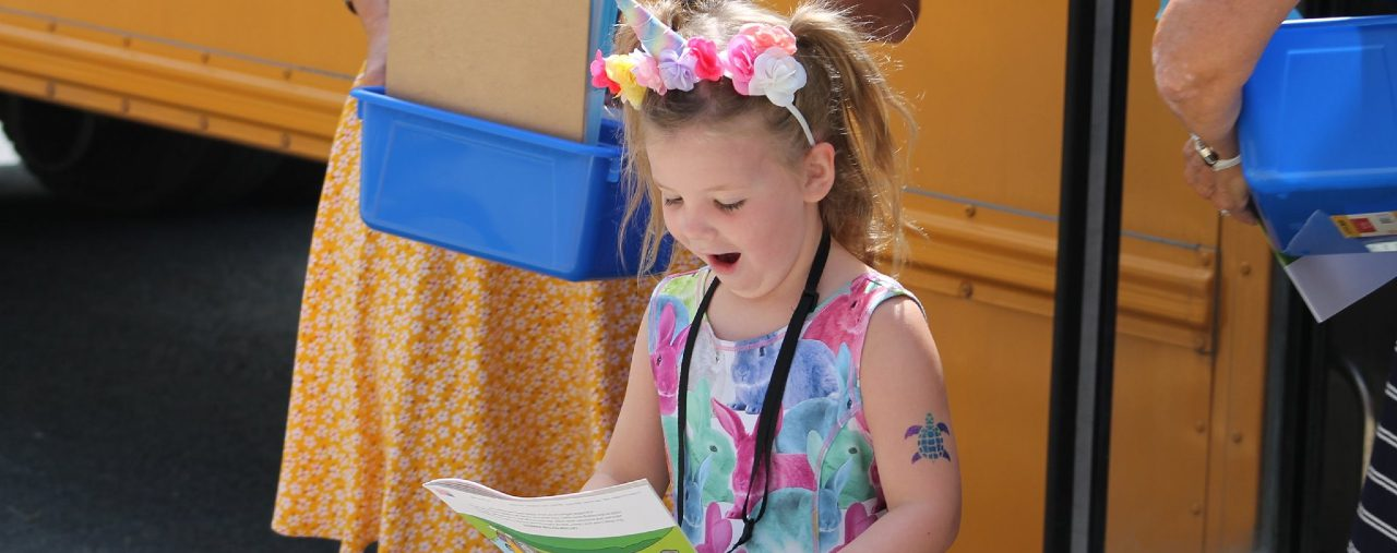 A very happy kindergarten girl receives a coloring book as she exits her first bus ride at kindergarten orientation