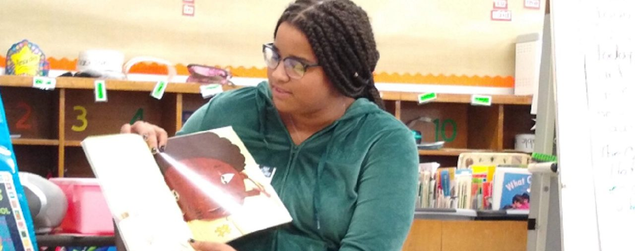 A high school student reads a book to a Montgomery Elementary School class
