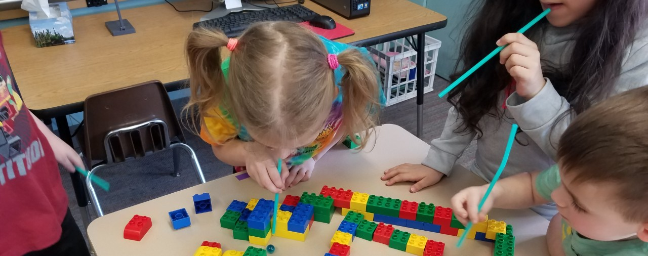 Elementary students working together on building a lego maze and using a straw to guide a marble through the maze.