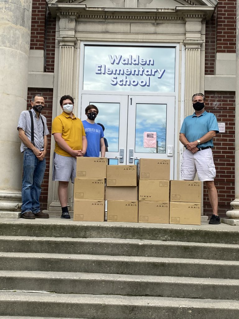 Walden Elementary Principal, Greg Heideman with boxes containing 518 books collected and donated  by Class of 2020 graduate Zach Kuenzi on the steps of the school.  Also pictured are Zach's father and brother.