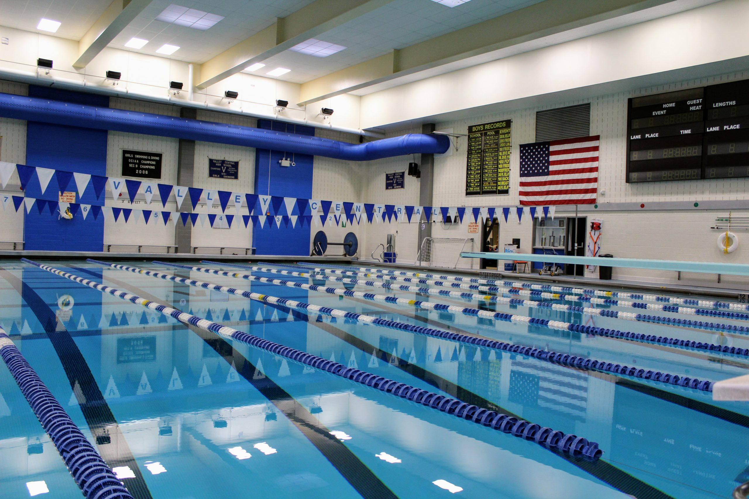 VC Pool showing the still water, lanes and deck with American Flag. There are blue and white flag banners above the water