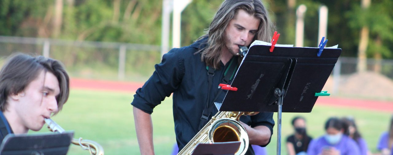 2 saxophonists playing during the hs pops concert outdoors on the track