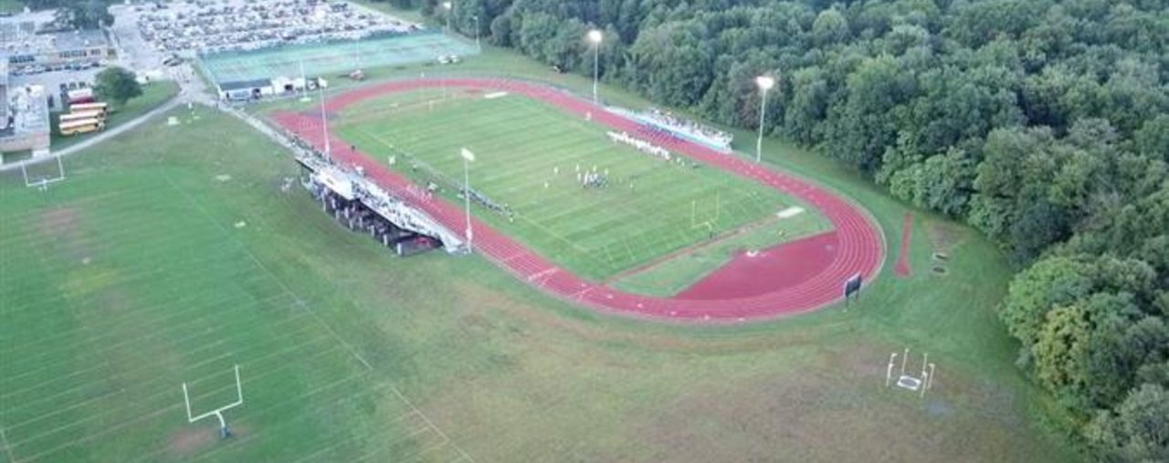 drone photo of the football field, stadium and track with the high school parking lot