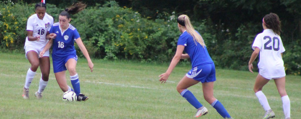 Girls soccer player edges out opponent for the ball as teammate is ready to assist